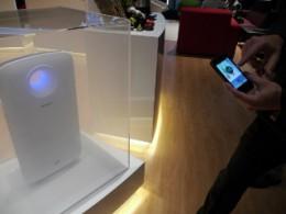 部屋に見立てた透明ケースの中にケムリを充満させ、スマホで空気清浄機能を作動させるようす